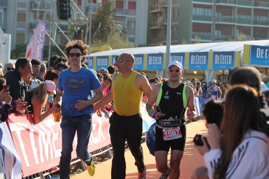 in mezzo a due ali di folla Bernardo mentre accompagna correndo l'arrivo del suo compagno di staffetta all'ironman di Pescara in cui Bernardini ha svolto la frazione di nuoto