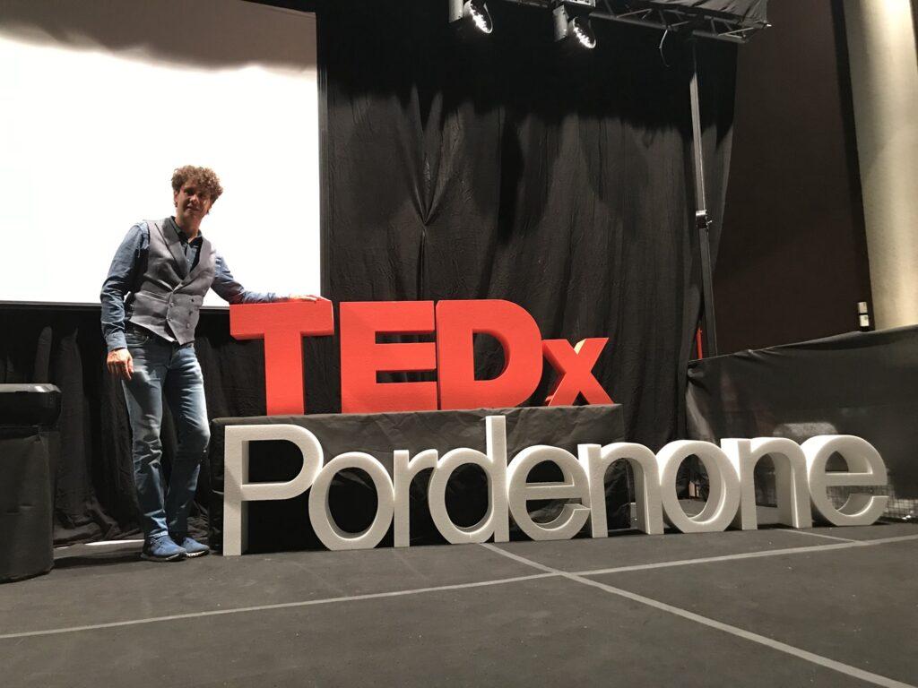 Bernardo posa di fianco alla scritta TedX Pordenone dopo aver fatto lo speech