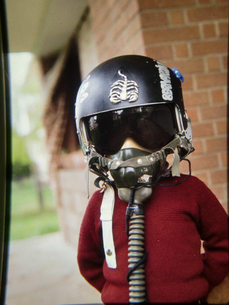 Bernardo bambino, a circa 6 anni, in giardino gioca indossando il casco da volo del padre Fausto e ha la visiera nera abbassata sugli occhi e la maschera dell'ossigeno chiusa sul viso