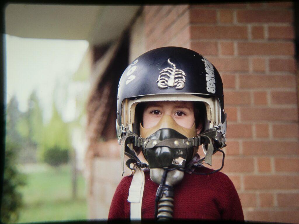 Bernardo in giardino di casa con indosso il casco del padre con la maschera dell'ossigeno chiusa e la visiera alzata, si vede lo sguardo felice