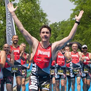 Bernardo con le braccia alzate al traguardo della gara di triathlon alle Bandie, la squadra lo accompagna. si vedono i tutori in carbonio toe off con cui riesce a correre