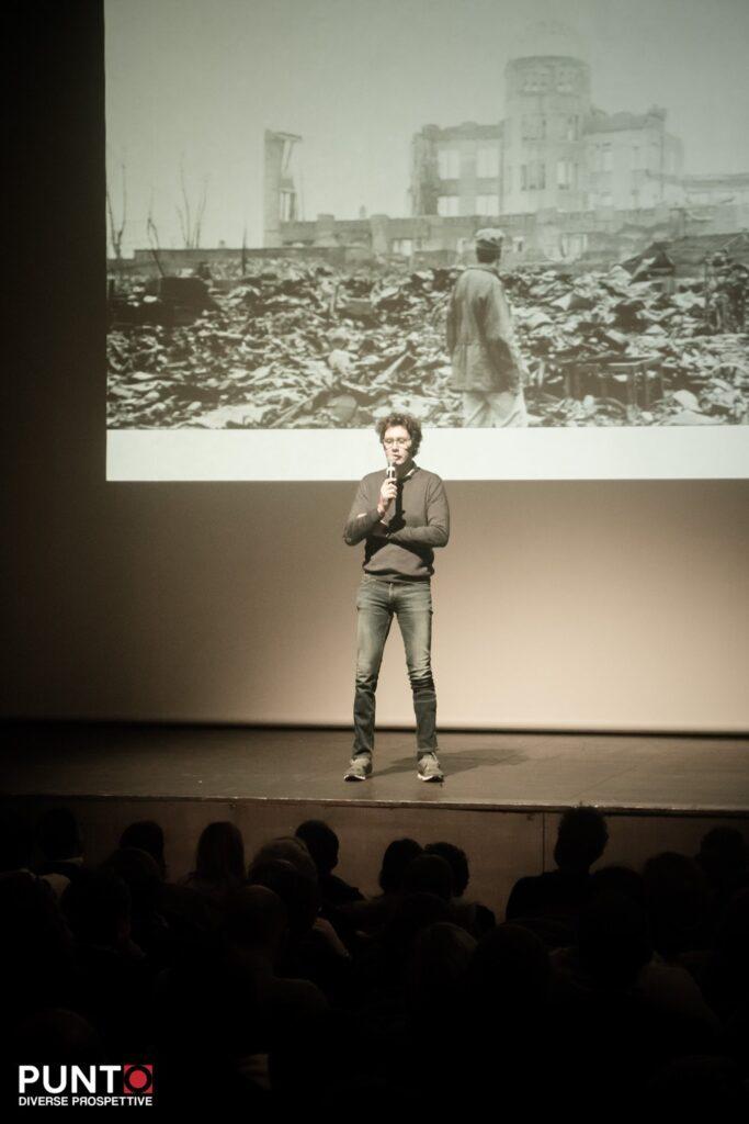 Bernardo sul palco di Punto diverse prospettive mentre paragona la devastazione provocata da un incidente traumatico alla devastazione lasciata dalla guerra