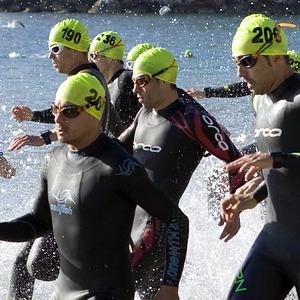 momento dell'ingresso in acqua alla partenza di una gara di triathlon, si vedono gli atleti che tutti assieme corrono verso le onde del mare