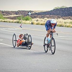 Nella foto si vedono due atleti che stanno svolgendo la finale del campionato del mondo di Ironman a Cona, nelle Hawai. Sono un atleta normo dotato e un atleta disabile, impegnati nella frazione di bicicletta
