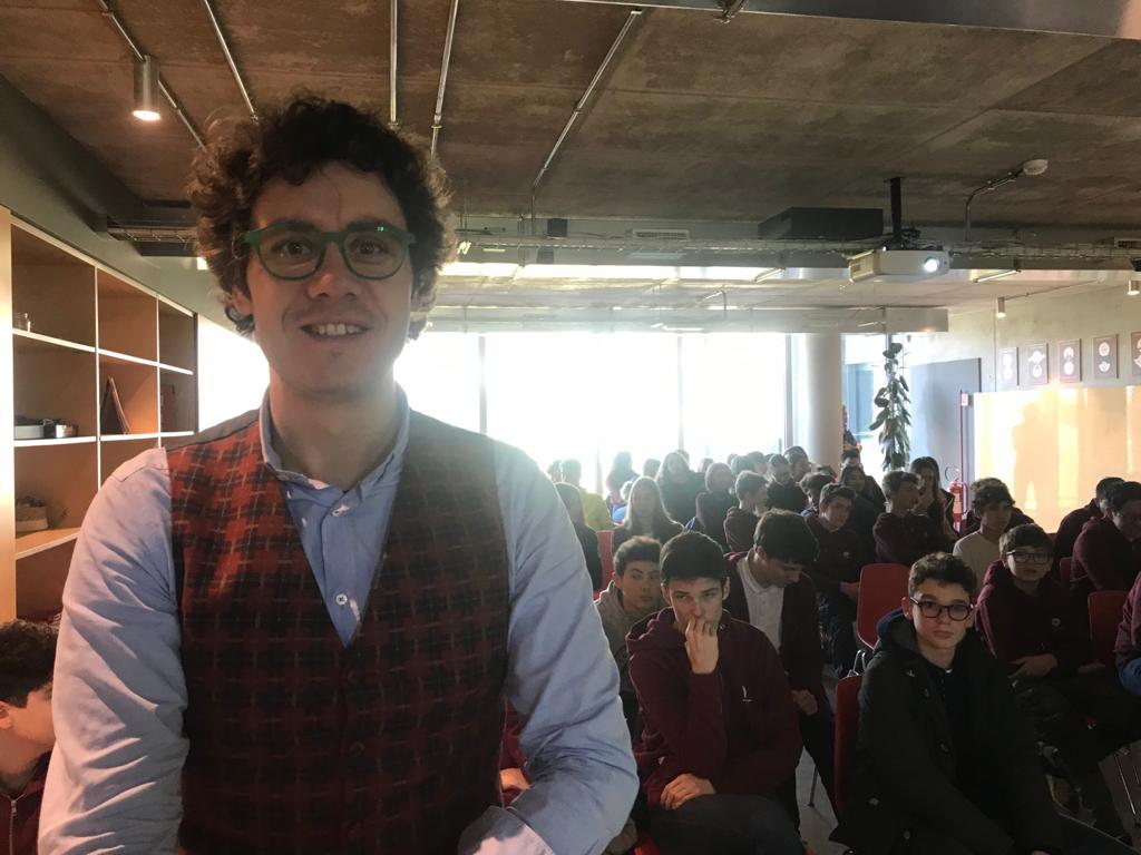 Bernardo sorridente a H Farm con gli studenti alle sue spalle